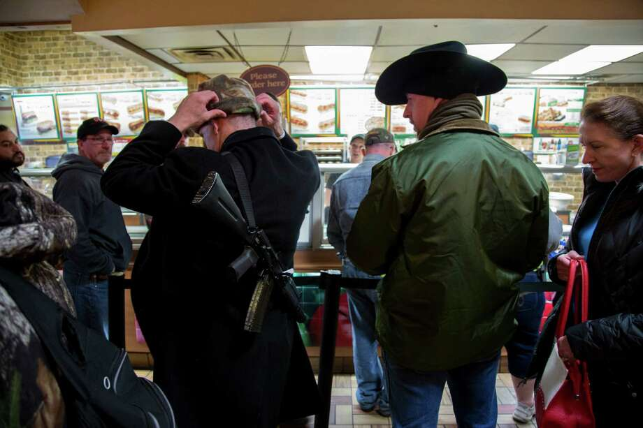 Andrew Clements, 36, carries an assault rifle on his back while waiting in line at a Subway restaurant following a rally about expanded gun rights in downtown Austin, Texas, Jan. 1, 2016. Photo: ILANA PANICH-LINSMAN / NYTNS