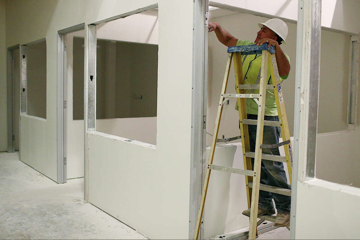 Alfredo Almanza trims wallboard at Bexar County's future Video Visitation and Re-entry Center, located in the jail's South Annex on Comal Street, in November. The center could open in May.