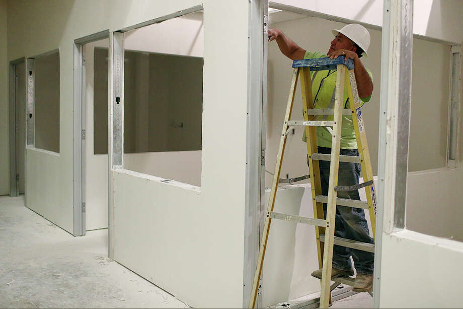 Alfredo Almanza trims wallboard at Bexar County's future Video Visitation and Re-entry Center, located in the jail's South Annex on Comal Street, in November. The center could open in May. Photo: Photos By Jerry Lara /San Antonio Express-News / © 2015 San Antonio Express-News