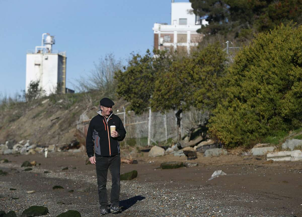 Peter Brooks, with the citizens group Fresh Air Vallejo, walks on a section of Sandy Beach in front of the old General Mills flour mill in Vallejo, Calif. on Thursday, Dec. 31, 2015. Residents are fighting a planned concrete plant and shipping terminal proposed on the site located directly across from Mare Island.