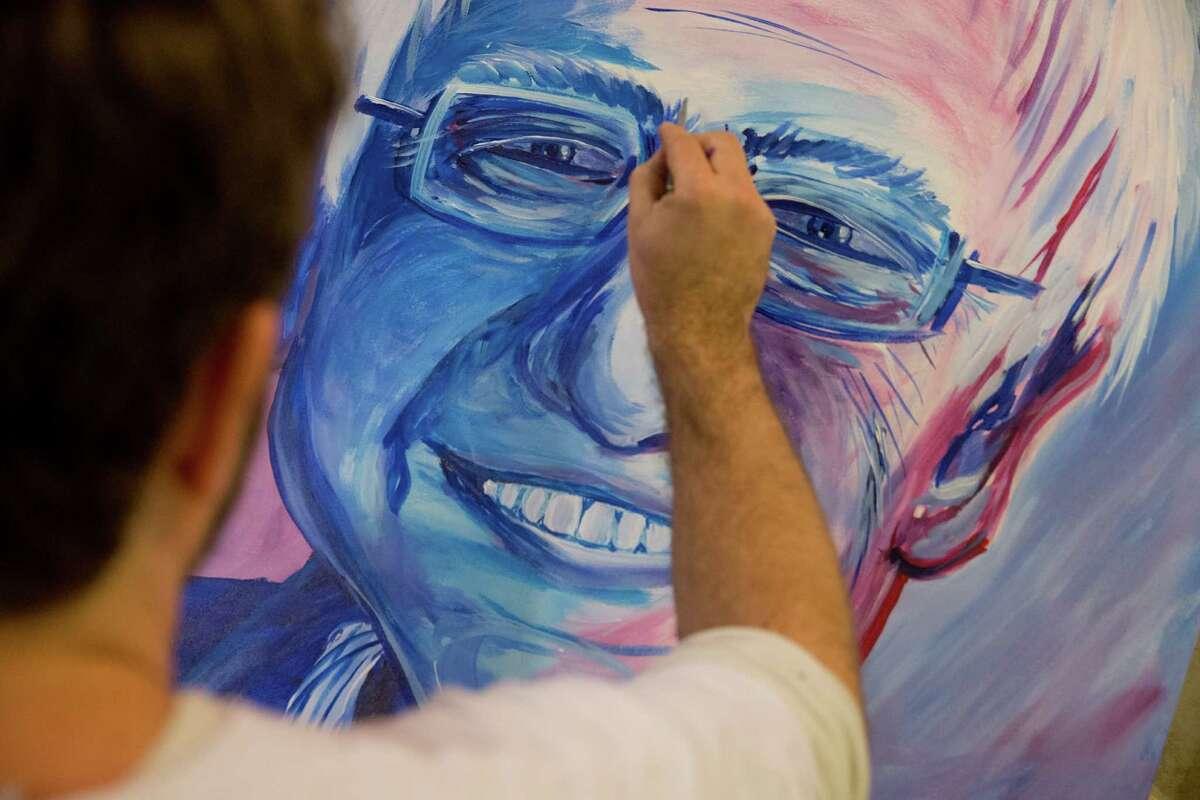 Rob Hogan paints a portrait of Sen. Bernie Sanders at his New Year's Eve party in Des Moines, Iowa.