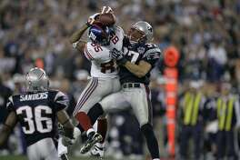 New York Giants receiver David Tyree (85) catches a 32 yard pass in the clutches of New England Patriots safety Rodney Harrison (37) during the fourth quarter of the Super Bowl XLII football game at University of Phoenix Stadium on Sunday, Feb. 3, 2008 in Glendale, Ariz. (AP Photo/Gene Puskar)
