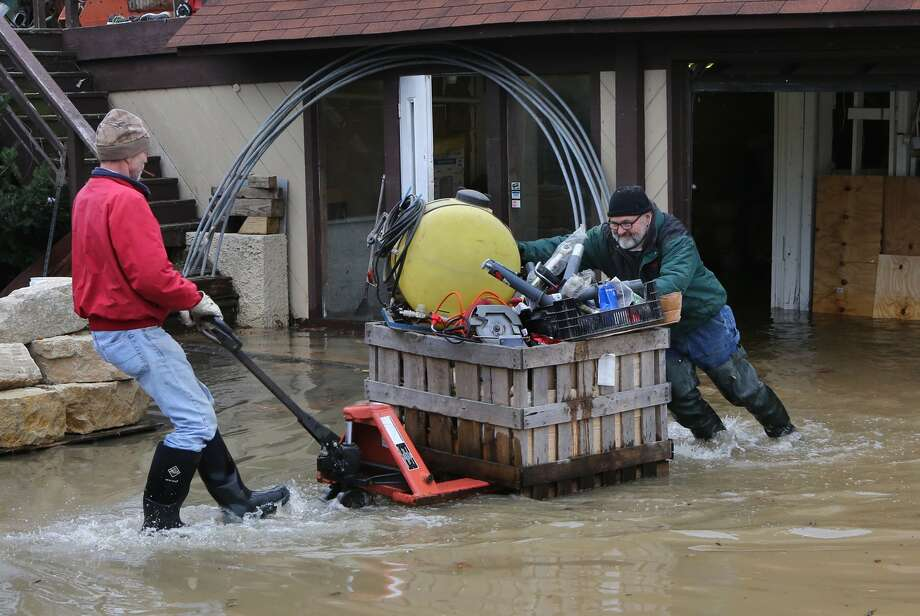 Mark Diehl, left, and Dale Atchley move items to higher ground at the Fenton Feed Mill on Tuesday, Dec. 29, 2015, in Fenton, Mo. Torrential rains over the past several days pushed already swollen rivers and streams to virtually unheard-of heights in parts of Missouri and Illinois. (J.B. Forbes /St. Louis Post-Dispatch via AP) Photo: J.B. Forbes /Associated Press / St. Louis Post-Dispatch