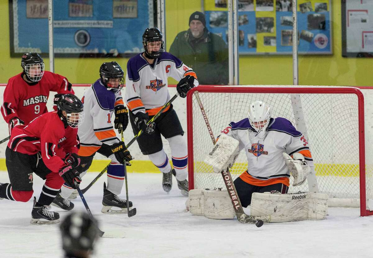The Westhill-Stamford co-op team goalie Christian Compolattarotries to get control of a loose puck in front ot the goal during a boys ice hockey game against Masuk High School played at Terry Connors Rink, Stamford, CT on Saturday, January 2, 2016.