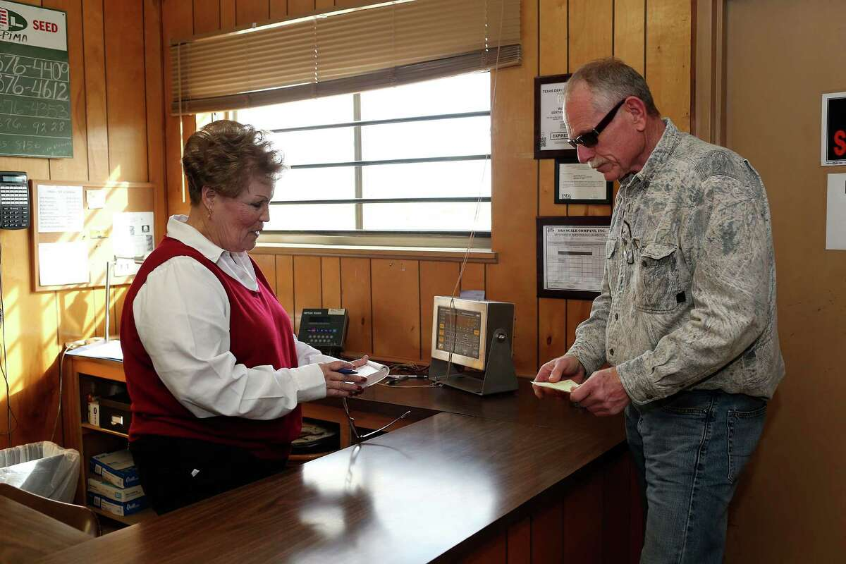 Richard Collier, Zavala County rancher, settles with Josie Prado, secretary at Leona Valley Gin as he picks up a load of cottonseed for deer feed at the gin near Batesville, Texas, Wednesday, Dec. 23, 2015. Collier owns a pipe company that sells to oil drilling companies. With the downturn in the oil business, his sales have dropped.
