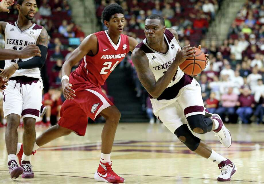 Texas A&M's Jalen Jones (12) drives past Arkansas' Jimmy Whitt (24) during an NCAA college basketball game Saturday, Jan. 2, 2016, in College Station, Texas. (AP Photo/Sam Craft) Photo: Sam Craft, FRE / Associated Press / FR145148 AP