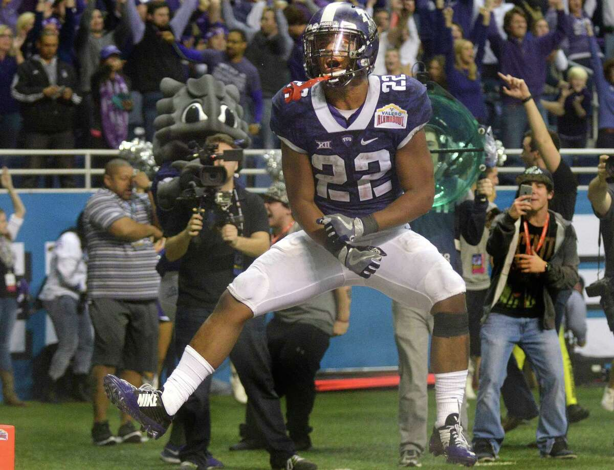 TCU running back Aaron Green celebrates after scoring a touchdown with just over three minutes to go in the fourth quarter to pull TCU to within a field goal of Oregon in Valero Alamo Bowl action in the Alamodome on Jan. 2, 2015. TCU won, 47-41.