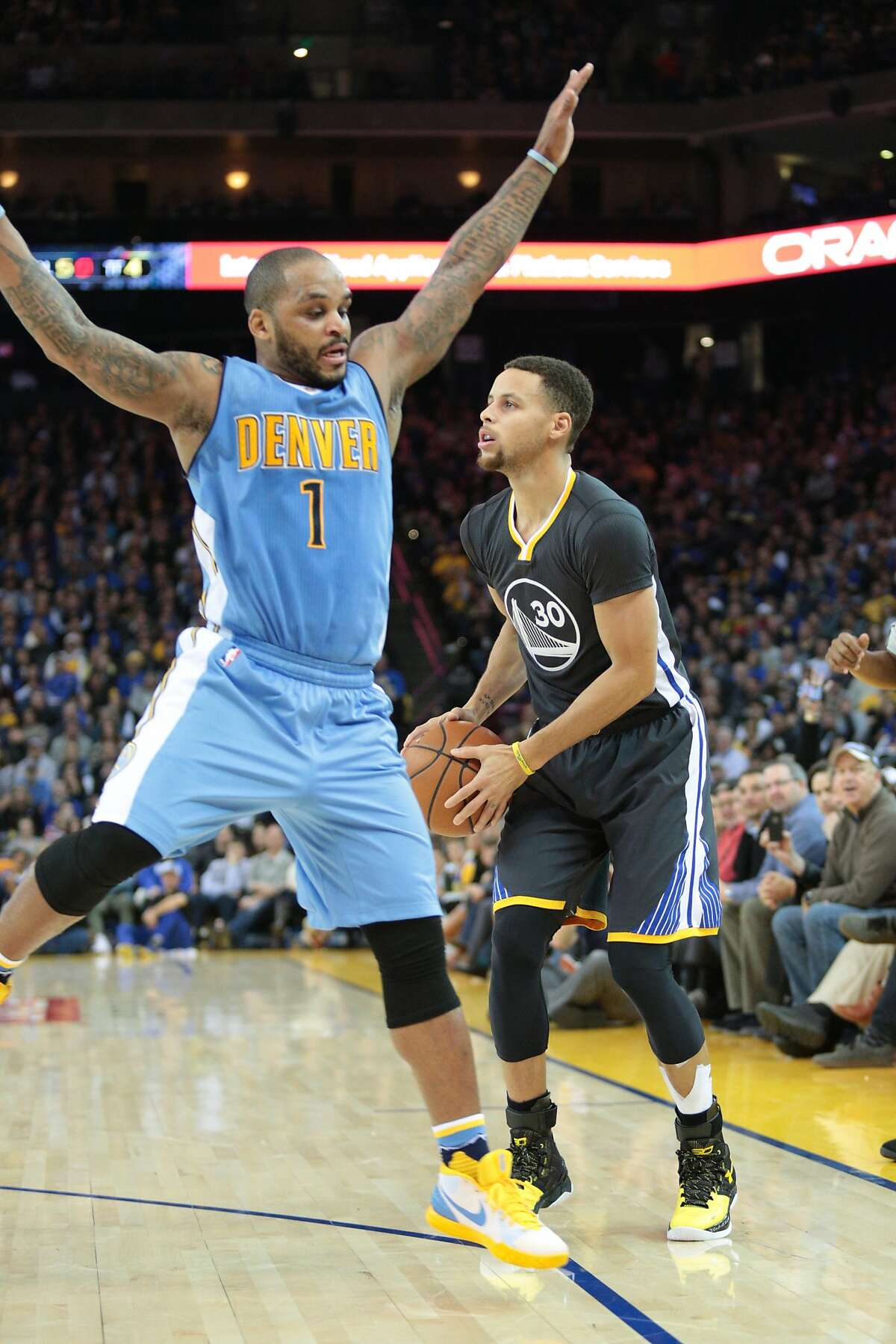Golden State Warriors guard Stephen Curry (30) fakes a shot against Denver Nuggets guard Jameer Nelson (1) during the first half of an NBA basketball game, Saturday, Jan. 2, 2016, at Oracle Arena in Oakland, Calif.