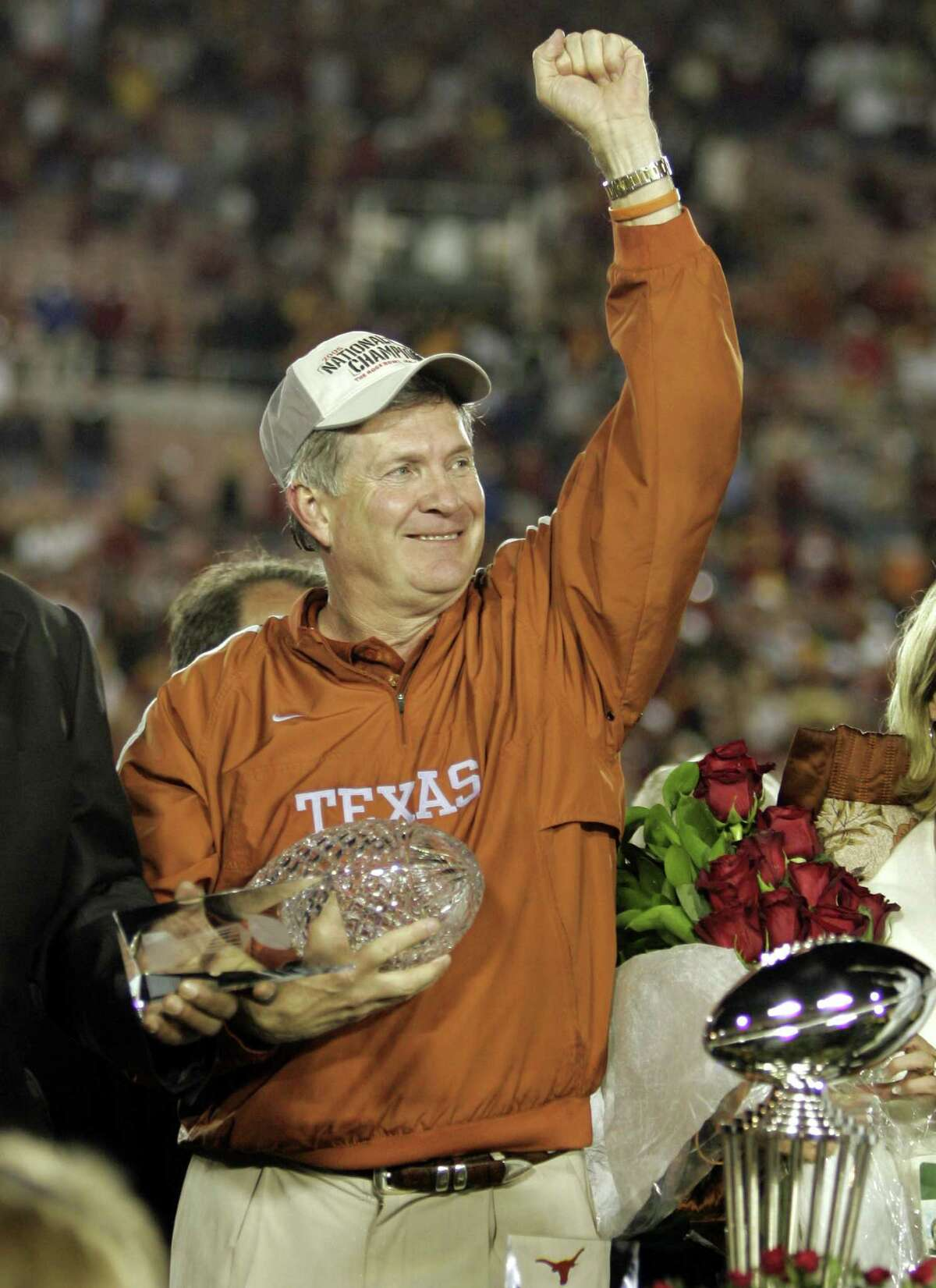FILE - In this Jan. 4, 2006, file photo, Texas head coach Mack Brown celebrates with the championship trophy after Texas beat Southern California 41-38 in the Rose Bowl, the national championship college football game in Pasadena, Calif. Brown has stepped down as coach and that the Alamo Bowl against Oregon on Dec. 30 will be his last game with the Longhorns, the school announced Saturday, Dec. 14, 2013. (AP Photo/ Mark J. Terrill, File)