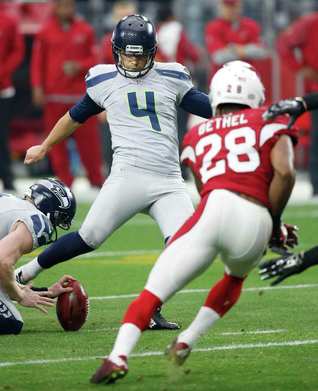 Seattle Seahawks kicker Steven Hauschka (4) kicks a field goals as Arizona Cardinals cornerback Justin Bethel (28) pursues during the first half of an NFL football game, Sunday, Jan. 3, 2016, in Glendale, Ariz. (AP Photo/Ross D. Franklin)