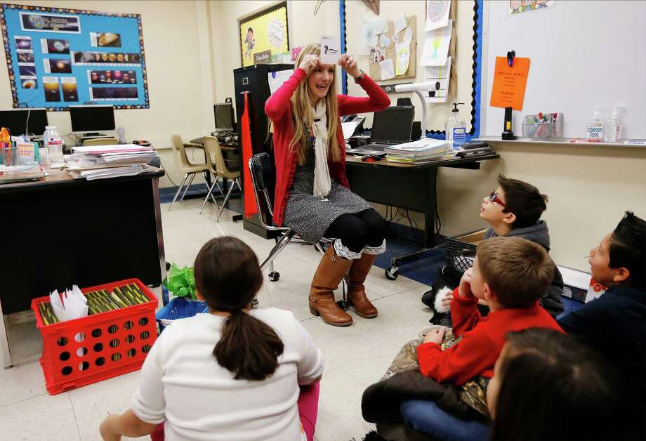 First-year teacher Paige Pitman leads fourth-grade students through an interactive lesson on how organisms adapt to survive in their environment during class at Boone Elementary on Thursday, Dec. 17, 2015. Pitman works with a mentor - a more seasoned teacher - to deal with any issues during her first year of teaching. (Kin Man Hui/San Antonio Express-News) Photo: Photos By Kin Man Hui / San Antonio Express-News / ©2015 San Antonio Express-News