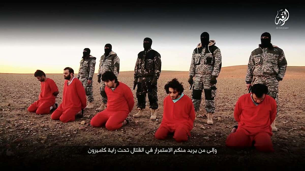 In this undated image taken from video posted online by Communications Arm of Islamic State group, circulating online Sunday Jan. 3, 2016, purporting to show members of the Islamic State group shooting five men who they accuse of spying for Britain in Syria. The video could not be independently verified, but the footage Sunday bears the markings of the IS media wing. No translation for Arabic script available.