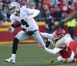 Oakland Raiders quarterback Derek Carr (4) is tackled by Kansas City Chiefs safety Ron Parker (38) during the first half of an NFL football game in Kansas City, Mo., Sunday, Jan. 3, 2016. (AP Photo/Charlie Riedel)