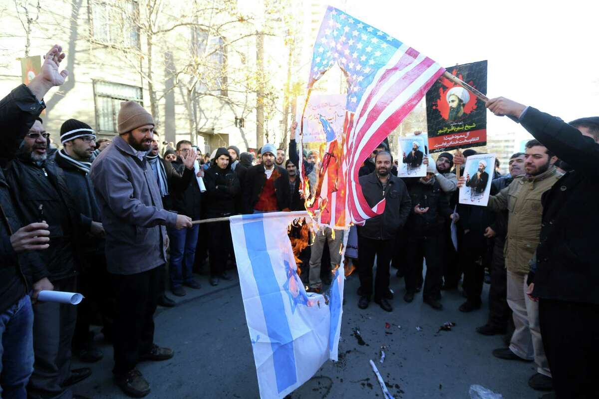 Iranian men burn Israeli and American flags during a demonstration against the execution of prominent Shiite Muslim cleric Nimr al-Nimr by Saudi authorities, on January 3, 2016, outside the Saudi embassy in Tehran. Iran and Iraq's top Shiite leaders condemned Saudi Arabia's execution of Nimr, warning ahead of protests that the killing was an injustice that could have serious consequences. AFP PHOTO / ATTA KENAREATTA KENARE/AFP/Getty Images