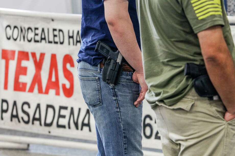 Marcus and Anthony Holcomb openly carry handguns at George R. Brown Convention Center. Photo: Michael Ciaglo, Staff / © 2016  Houston Chronicle