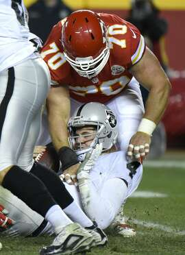 Kansas City Chiefs defensive end Mike DeVito (70) sacks Oakland Raiders quarterback Derek Carr (4) during the second half of an NFL football game in Kansas City, Mo., Sunday, Jan. 3, 2016. (AP Photo/Ed Zurga)