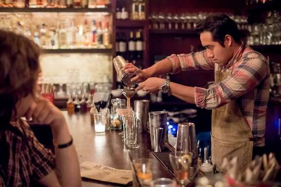 Bartender Daniel Godinez strains a drink at 15 Romolo in San Francisco, Calif., on January 2nd, 2016.