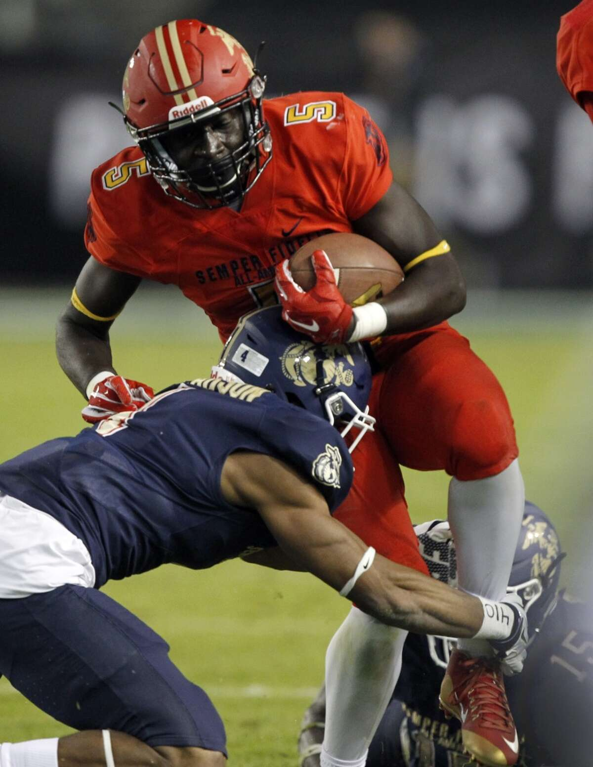 West running back D'Vaughn Pennamon, right, leaps into East corner back Zech McPherson, left, during the first half of the Semper Fidelis All-American Bowl East West high school football game in Carson, Calif., Sunday, Jan. 3, 2016. (AP Photo/Alex Gallardo)