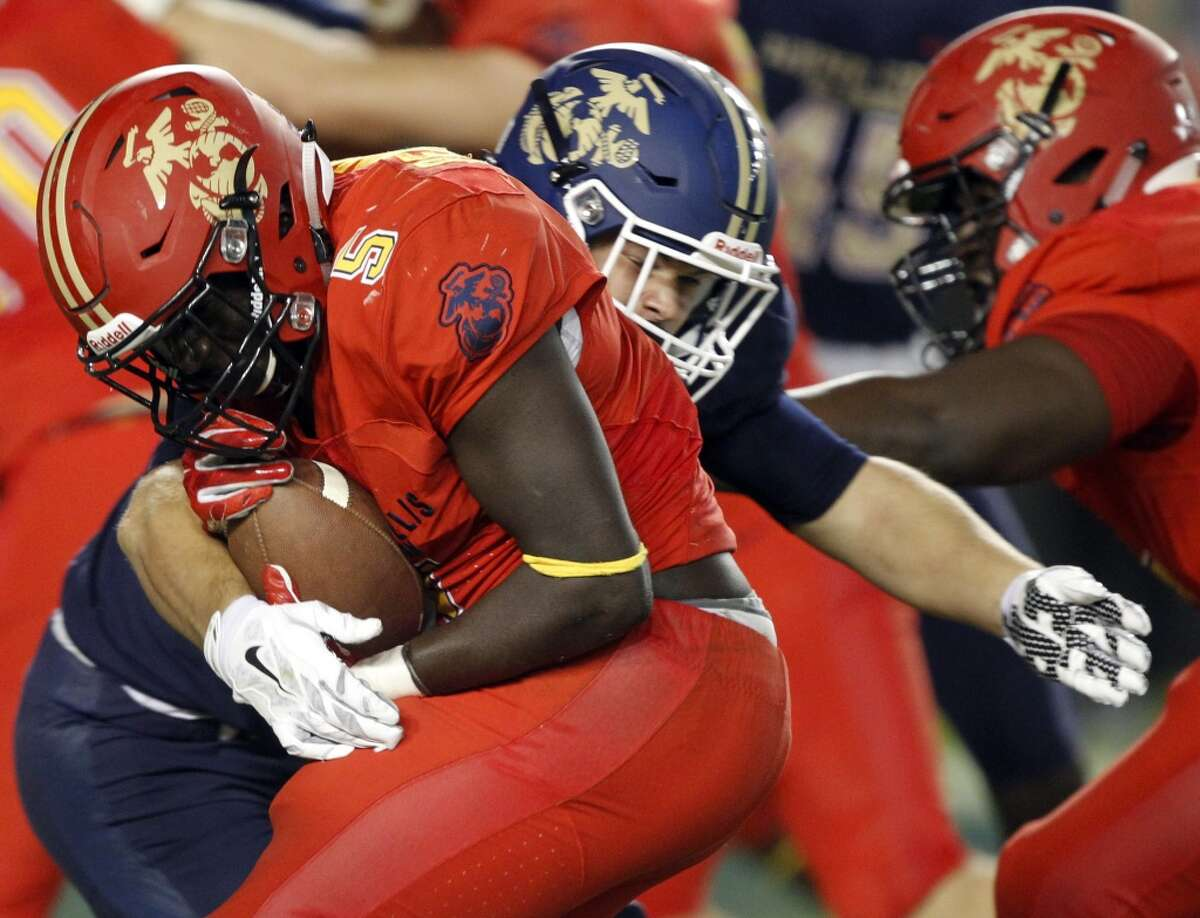 West running back D'Vaughn Pennamon (5) is stopped for no gain by East linebacker Joel Dublanko, center, during the second half of the Semper Fidelis All-American Bowl East West high school football game in Carson, Calif., Sunday, Jan. 3, 2016. The East won 28-13. (AP Photo/Alex Gallardo)