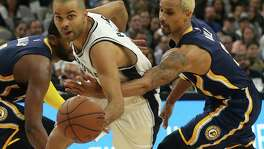 Indiana Pacers' George Hill attempts to steal the ball from San Antonio Spurs' Tony Parker during the second half at the AT&T Center, Monday, Dec. 21, 2015. The Spurs won, 106-92.