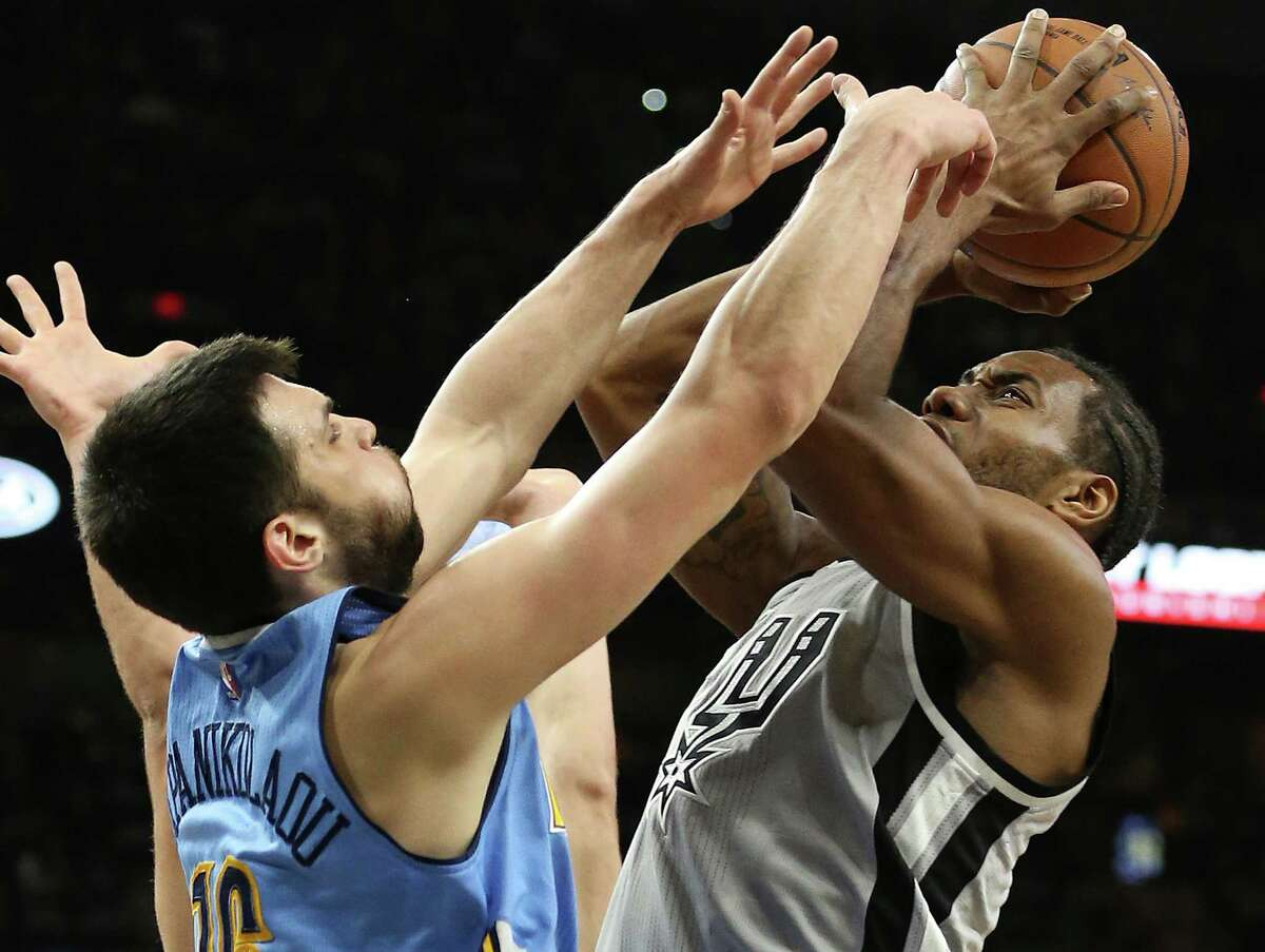 Kawhi Leonard challenges Kostas Papanikolaou in the lane as the Spurs host the Denver Nuggets at the AT&T Center on December 27, 2015.