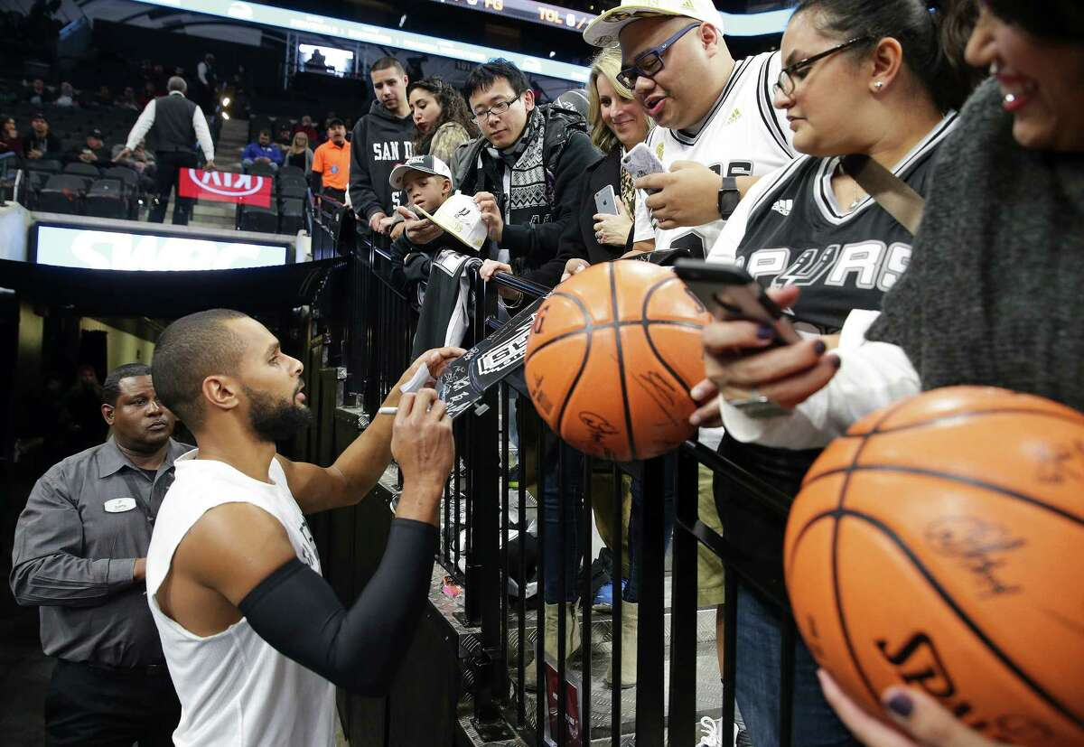 Patty Mills obliges autograph seekers before game time as the Spurs host the Minnesota Timberwolves at the AT&T Center on December 28, 2015.