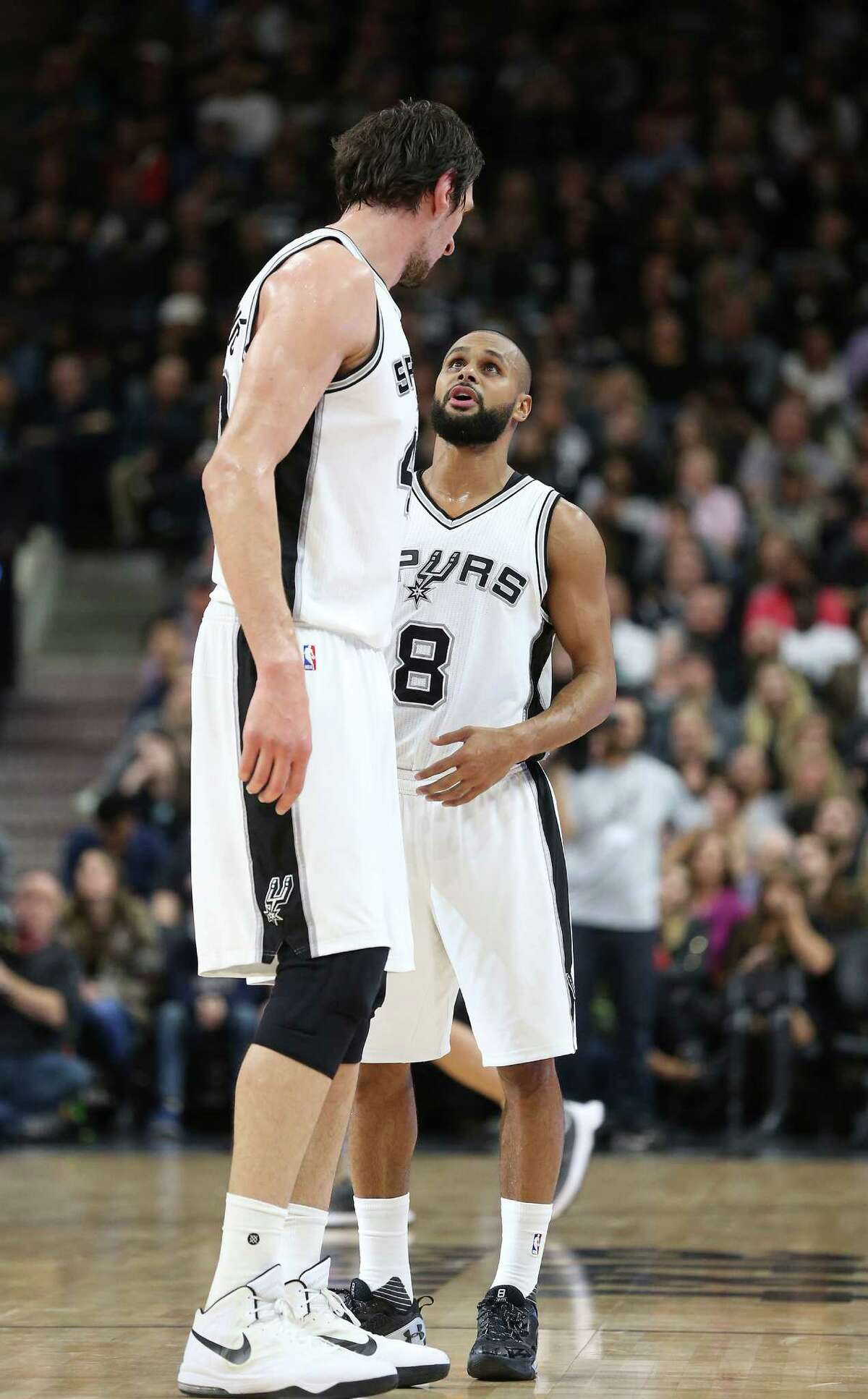 Patty Mills confers with Boban Marjanovic as the Spurs host the Suns at the AT&T Center on December 30, 2015.