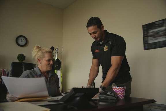 Detective Lori Morgan and Detective Aubrey St. Angelo examine evidence.