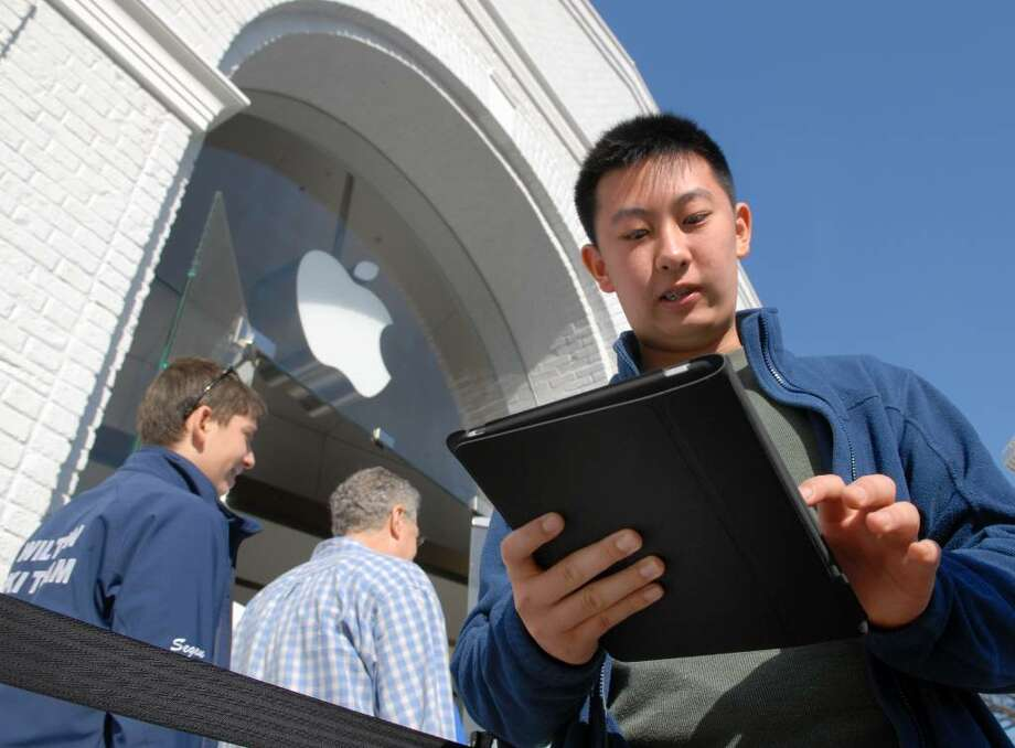 Eric Li, 14, of Old Greenwich, fires up his new iPad outside the Apple Store on Greenwich Ave., Saturday morning, April 3rd, 2010, on the first day that the iPad was available for purchase. Photo: Bob Luckey / Greenwich Time