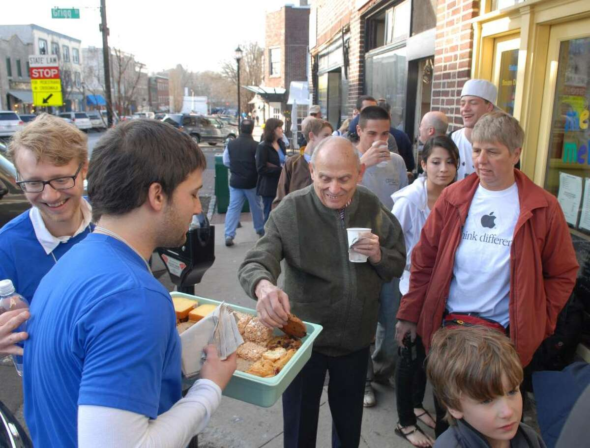 John Tishman of NYC grabs a free cookie from an Apple employee named, Mike (Mike was not allowed to give his last name), as Apple employees handed out free coffe and pastries during the launch of Apple's new mobile computing device known as the iPad, at the Apple store on Greenwich Ave., Saturday morning, April 3rd, 2010, Greenwich, Conn.