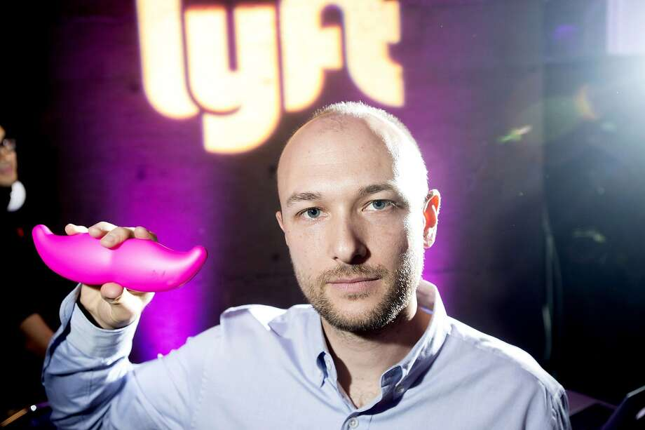 """FILE - In this Monday, Jan. 26, 2015, file photo, Logan Green, co-founder and chief executive officer of Lyft, displays his company's """"glowstache"""" during a launch event in San Francisco. On Monday, Jan. 4, 2016, General Motors Co. announced it is investing $500 million in ride-sharing company Lyft Inc. GM gets a seat on Lyft's board as part of the partnership, which could speed the development of on-demand, self-driving cars. (AP Photo/Noah Berger, File) Photo: Noah Berger, Associated Press"""