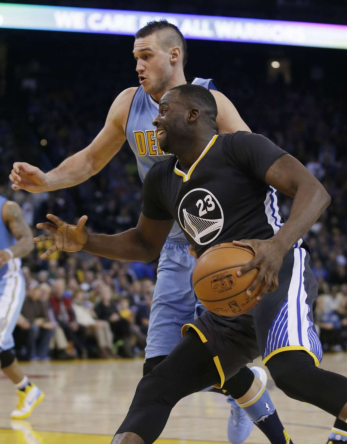 Draymond Green (23) dribbles next to Denver Nuggets' Danilo Gallinari during the second half of an NBA basketball game Saturday, Jan. 2, 2016, in Oakland, Calif. Golden State won 111-108 in overtime. (AP Photo/Marcio Jose Sanchez)