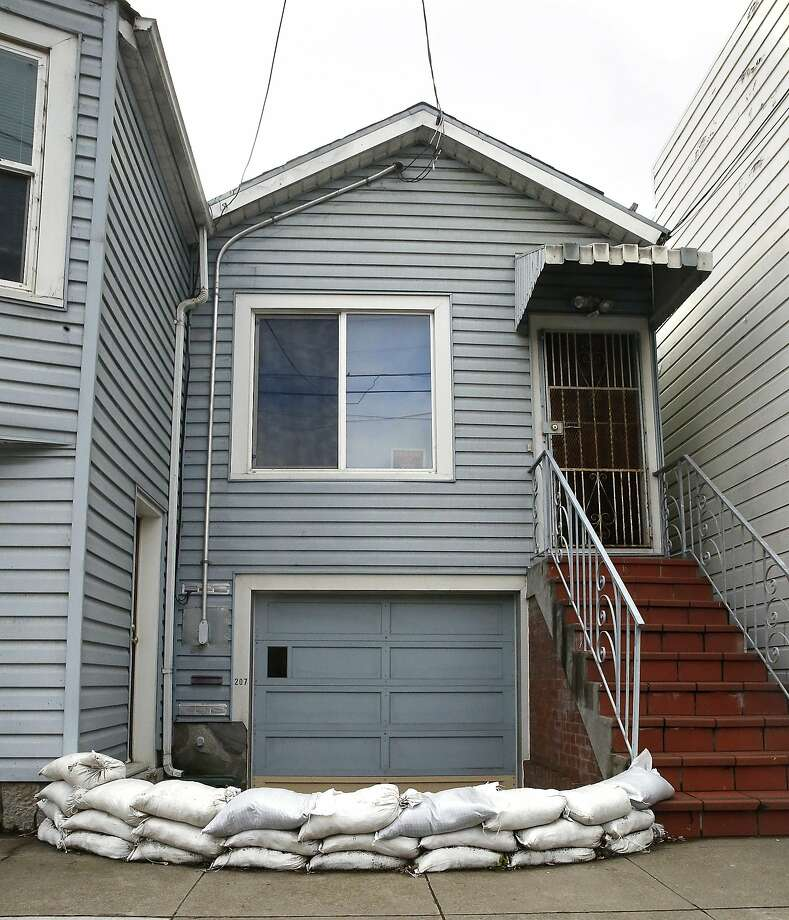 Sandbags border a garage door below street level on Cotter St. near Cayuga Ave. in San Francisco, California, before heavy rains expected this week on Monday, January 4, 2015. Photo: Liz Hafalia, The Chronicle