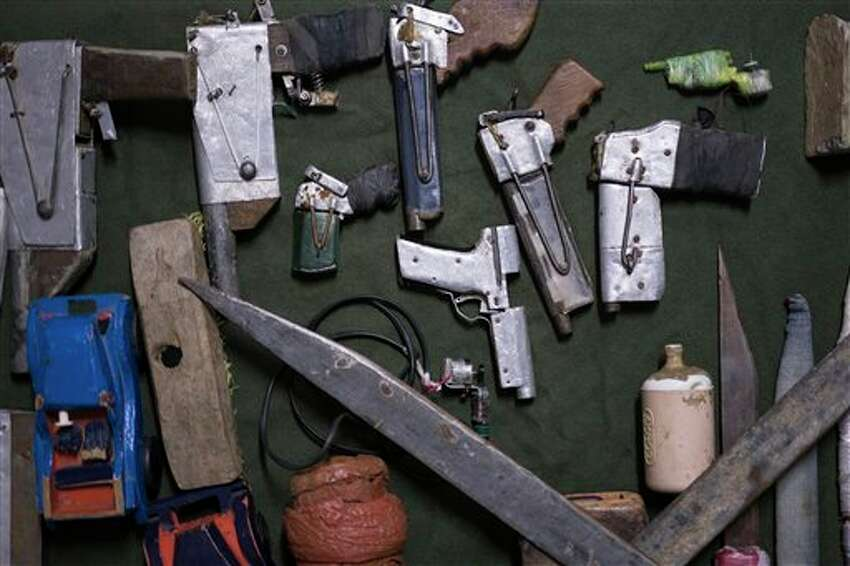 In this Dec. 1, 2015 photo, handmade weapons and tools found in inmates' cells lay on display at the Central Prison in Porto Alegre, Brazil. A recently installed scanner has reduced the number of cell phones, drugs and razor blades that are smuggled into the prison by visiting relatives. But many of these items are often thrown over the prison walls and retrieved by waiting inmates.