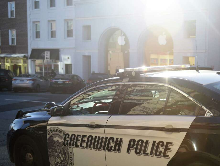A police car is parked across the street from the Apple Store along Greenwich Avenue in Greenwich, Conn. shortly after someone fled the store with Apple products on the afternoon of Monday, Jan. 4, 2016. Photo: Tyler Sizemore / Hearst Connecticut Media / Greenwich Time