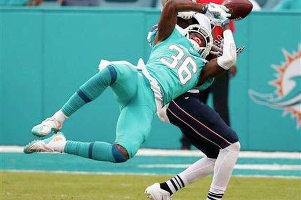 El defensivo de los Dolphins de Miami, Tony Lippett (36), intenta interceptar un pase lanzado al receptor de los Patriots de Nueva Inglaterra, Brandon LaFell (19), durante la segunda mitad del partido de la NFL el domingo 3 de diciembre de 2016, en Miami Gardens, Florida. (Foto AP/Wilfredo Lee)