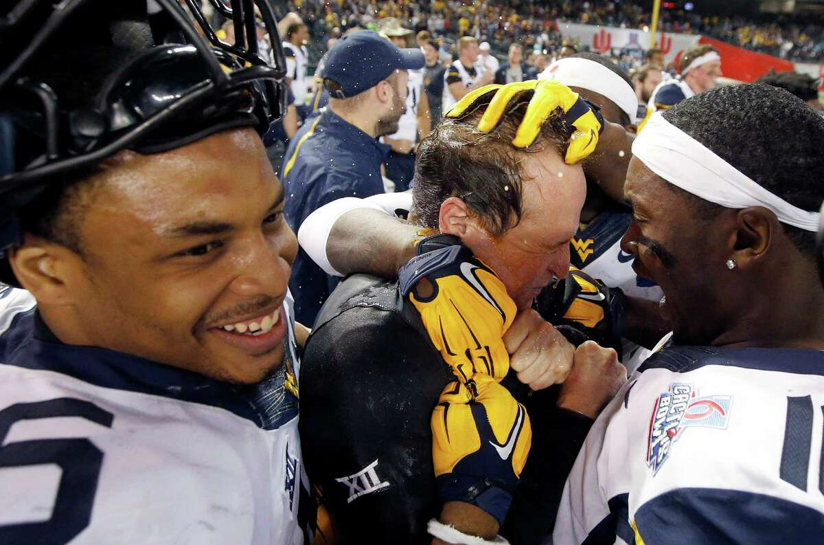 West Virginia head coach Dana Holgorsen, middle, celebrates a win after the Cactus Bowl NCAA college football game against Arizona State with Terrell Chestnut, left, and William Crest Jr., right, on Jan. 3, 2016, in Phoenix. West Virginia won 43-42.