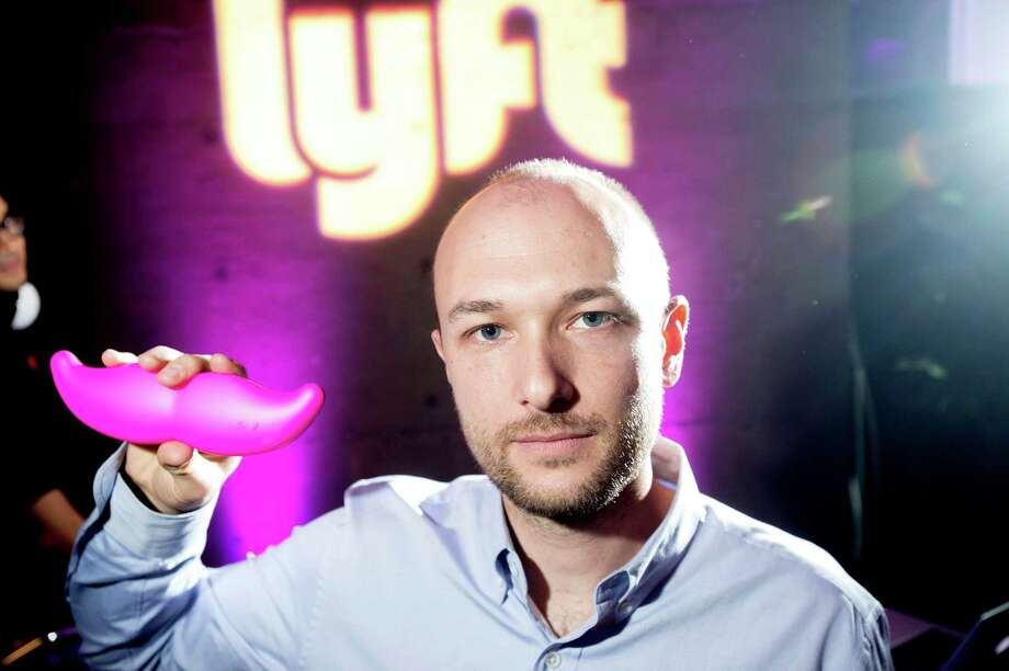 """FILE - In this Monday, Jan. 26, 2015, file photo, Logan Green, co-founder and chief executive officer of Lyft, displays his company's """"glowstache"""" during a launch event in San Francisco. On Monday, Jan. 4, 2016, General Motors Co. announced it is investing $500 million in ride-sharing company Lyft Inc. GM gets a seat on Lyft's board as part of the partnership, which could speed the development of on-demand, self-driving cars. (AP Photo/Noah Berger, File) ORG XMIT: NYBZ145 Photo: Noah Berger / FR34727 AP"""