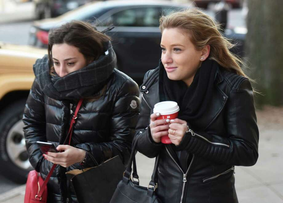Ella Bonime, left, of Scarsdale, N.Y., and Rebecca Fischer, of Rockland County, N.Y., brave the cold with scarves and hot coffee while walking down Greenwich Avenue in downtown Greenwich, Conn. Monday, Jan. 4, 2016. Greenwich bundled up Monday, with heavy wind and a high temperature barely topping 30 degrees. Photo: Tyler Sizemore / Hearst Connecticut Media / Greenwich Time