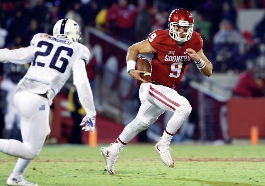 Oklahoma quarterback Trevor Knight (9) runs as TCU safety Derrick Kindred (26) closes in during the fourth quarter of an NCAA college football game in Norman, Okla., Saturday, Nov. 21, 2015. Oklahoma won 30-29. Photo: Alonzo Adams /Associated Press / FR159426 AP