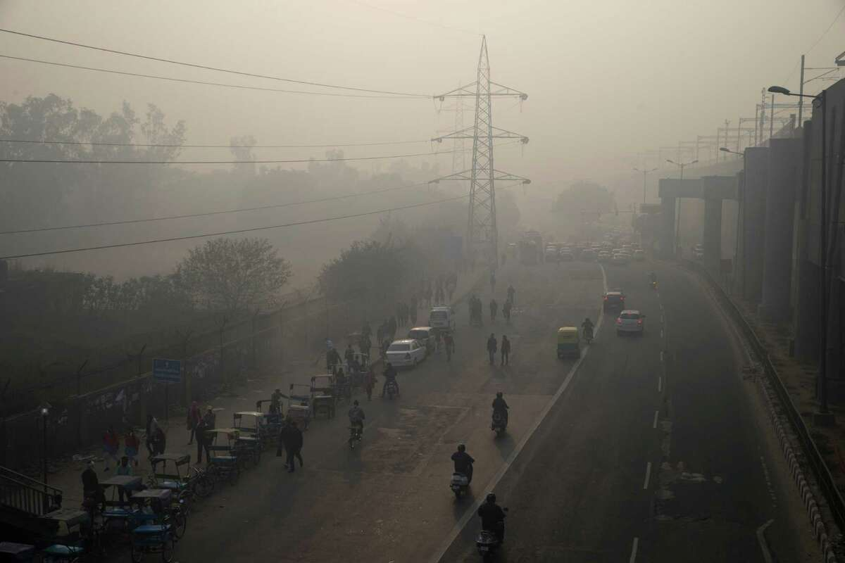 Smog envelops a roadway recently during an experiment to cut traffic to fight pollution in New Delhi, India.
