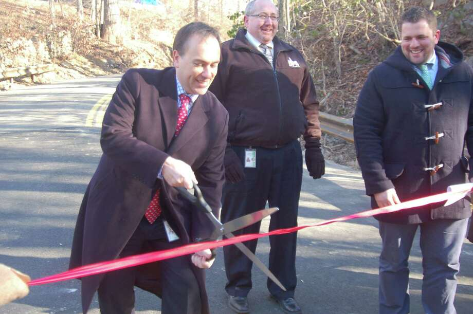 First Selectman Peter Tesei cuts a ribbon to the newly reopened West Old Mill Road Bridge in Greenwich Monday. The bridge had undergone a six-month rehabilitation project. Deputy DPW Commissioner James Michel, center, and Senior Civil Engineer Frank Petise stand in the background. Photo: Ken Borsuk / Hearst Connecticut Media / Greenwich Time