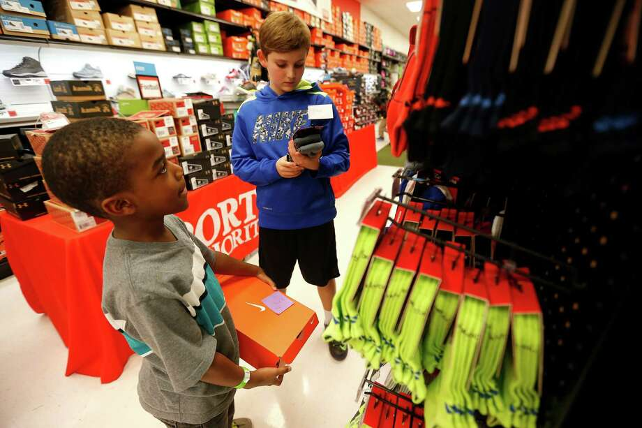 Ethan Holmes, 11, right, helps a child pick out socks to go with his shoes, as 70 children aged 4-17 from the Star of Hope's Randy and Kathy Tabor Transitional Living Center shop for new shoes at Houston's Sports Authority store on Post Oak, assisted by Trees of Hope Guild on Monday, Jan. 4, 2016, in Houston. Photo: Karen Warren, Houston Chronicle / © 2015  Houston Chronicle