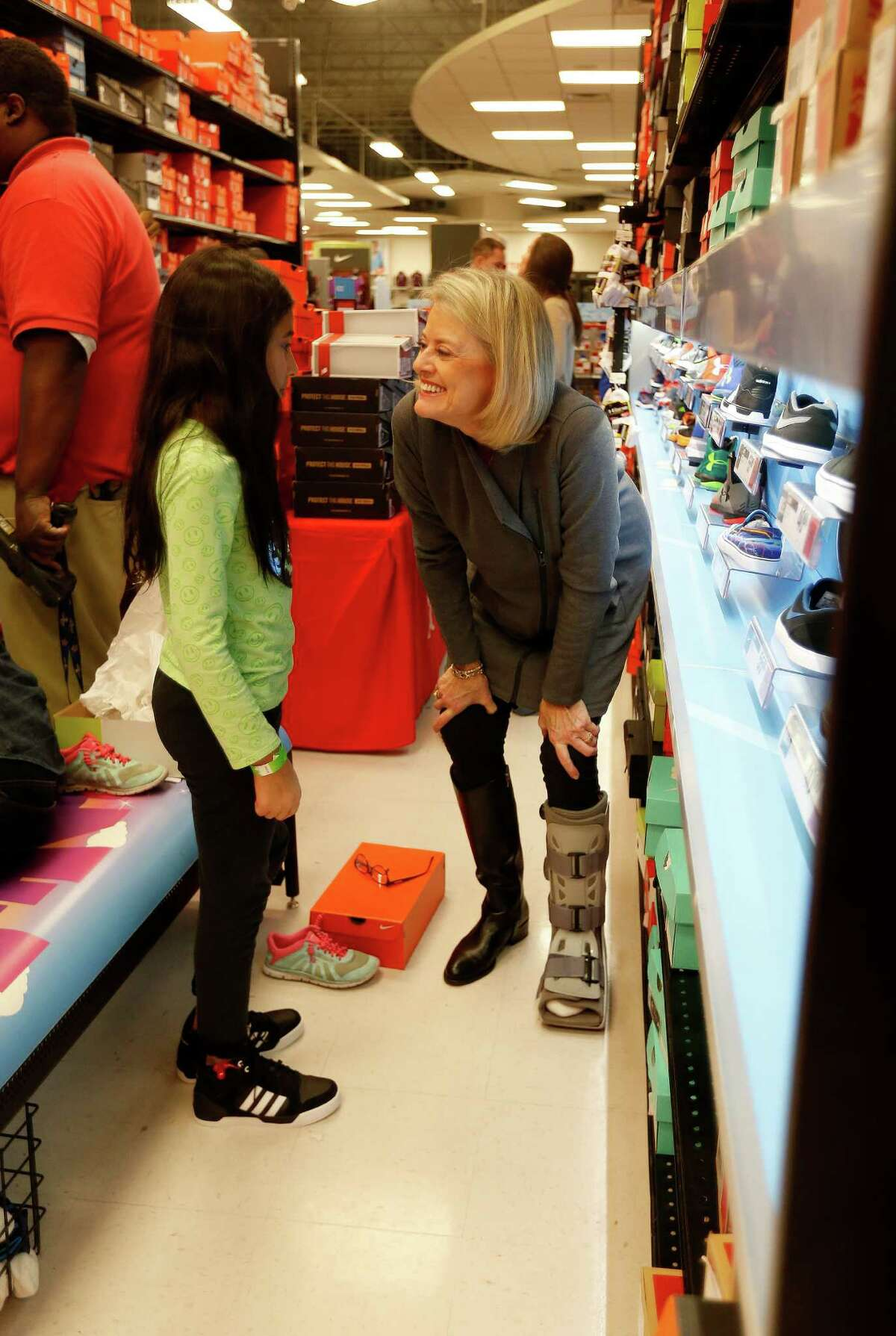 Sara Wilson helps Aalyah shop for shoes as she and about 70 children aged 4-17 from the Star of Hope's Randy and Kathy Tabor Transitional Living Center shop for new shoes at Houston's Sports Authority store on Post Oak, assisted by Trees of Hope Guild on Monday, Jan. 4, 2016, in Houston.