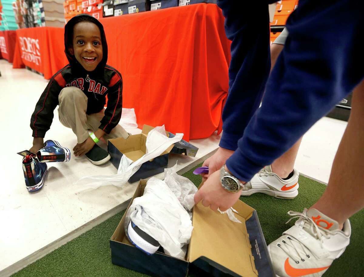 Christopher tries on Star Wars shoes with the help of Cullen Stewart, 14, as he and about 70 children aged 4-17 from the Star of Hope's Randy and Kathy Tabor Transitional Living Center shop for new shoes at Houston's Sports Authority store on Post Oak, assisted by Trees of Hope Guild on Monday, Jan. 4, 2016, in Houston.
