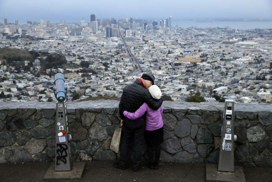 Kristyna Martincova, right, and Premysl Balaz from the Czech Republic share a kiss on Twin Peaks in San Francisco, Calif., on Monday, January 4, 2016.  Michael Hofman and Janet Moyer walk up Twin Peaks three times a week. In the last five years they've started picking up purses and backpacks from auto breakins. The twist is that they work hard to get the drivers' license or purse back to the owner. Last weekend they were three for three. Photo: Carlos Avila Gonzalez, The Chronicle