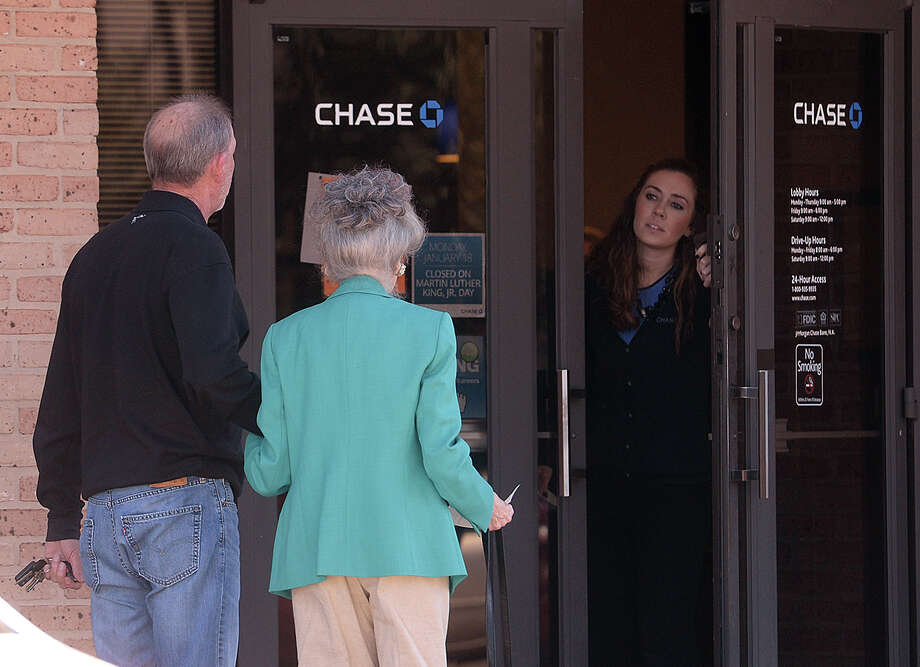 A masked gunman robbed the Chase bank on Dowlen Road and Phelan Boulevard Monday morning. Pictured, an employee informs two customers the bank is closed after the robbery. No injuries were reported from the incident. 