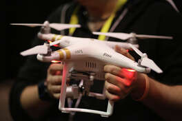 A DJI drone is held at The CES Unveiled press event, January 4, 2016 in Las Vegas, Nevada ahead of the CES 2016 Consumer Electronics Show.  CES, the annual consumer electronics and consumer technology trade show in Las Vegas boasts some 2.2 million net square feet of exhibition space.