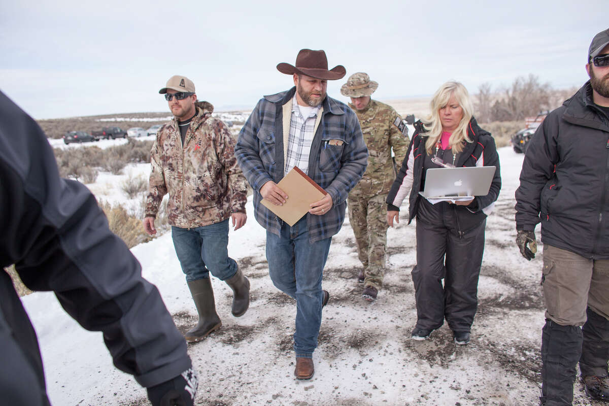 Ammon Bundy(C), leader of a group of armed anti-government protesters, arrives to speak to the media at the Malheur National Wildlife Refuge near Burns, Oregon January 4, 2016. The FBI on January 4 sought a peaceful end to the occupation by armed anti-government militia members at a US federal wildlife reserve in rural Oregon, as the standoff entered its third day. The loose-knit band of farmers, ranchers and survivalists -- whose action was sparked by the jailing of two ranchers for arson -- said they would not rule out violence if authorities stormed the site, although federal officials said they hope to avoid bloodshed. AFP PHOTO / ROB KERR / AFP / ROB KERR