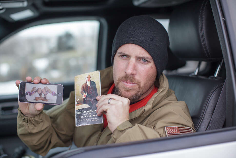 Jon Ritzheimer, 32, shows a family picture on his phone and a copy of the US Constitution to the media at  the Malheur National Wildlife Refuge Headquarters near Burns, Oregon,  Jan. 4, 2016. He is now unhappy how some of you have responded. Photo: ROB KERR, AFP/Getty Images / AFP